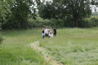 People in a field exploring Hardwick Green Meadows by Wendy Carter